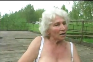 granny norma outdoors with large toys and a suck